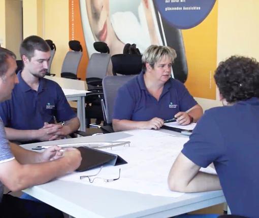 Vier Leute sitzen an einem Tisch und beraten sich