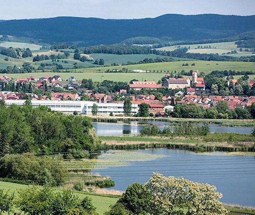 Landschaft mit See und Häusern
